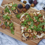 Ricotta caramelized onion and fig flatbread on a wooden board