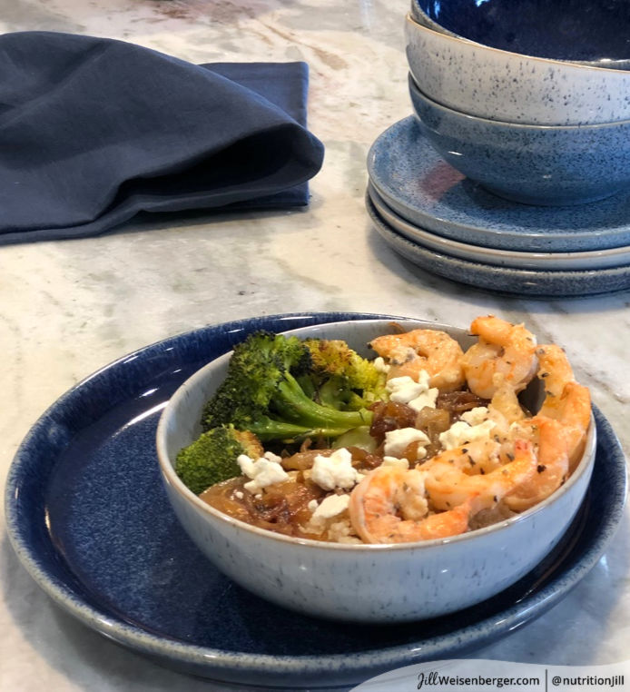 Nourish bowl with shrimp, whole grains, onions, broccol and feta cheese